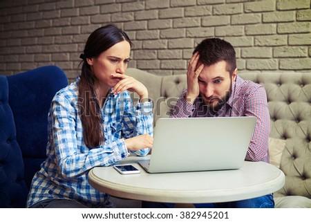 portrait of despondent couple looking at laptop - stock photo