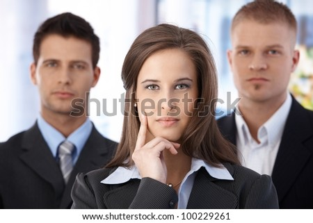 Portrait of determined business team, focus on attractive businesswoman. - stock photo