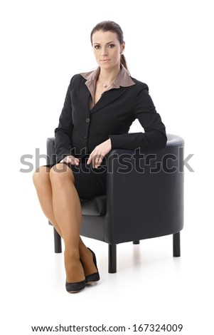 Portrait of determined businesswoman sitting in armchair, looking at camera, isolated on white. - stock photo