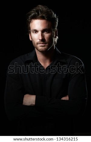 Portrait of determined goodlooking man wearing black shirt, black background. - stock photo