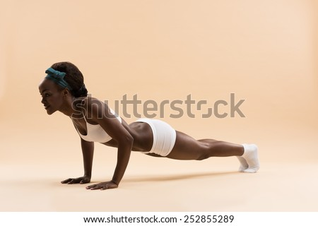 Portrait of determined young african woman doing push ups - stock photo