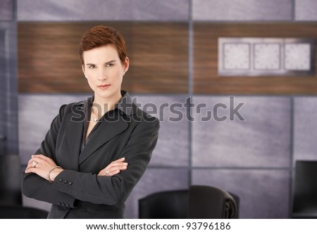 Portrait of determined young businesswoman in smart suit standing with arms folded in office, copyspace.? - stock photo