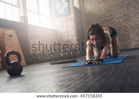 Portrait of determined young female athlete working out on exercise mat at gym. Focused woman stretching on fitness mat.