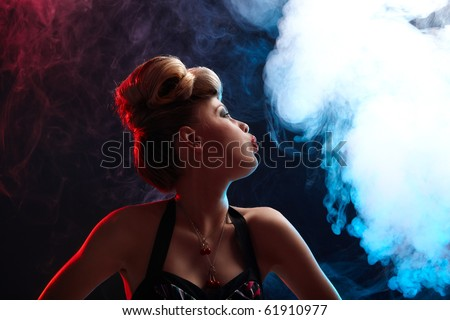 Portrait of diabolic woman with red and blue lights in smoke - stock photo