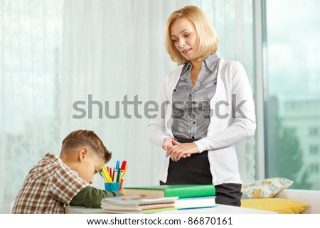 Portrait of diligent boy drawing at home with his tutor near by - stock photo