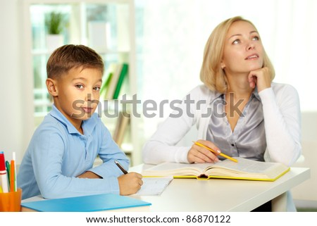 Portrait of diligent boy looking at camera at workplace with his tutor sitting on background - stock photo