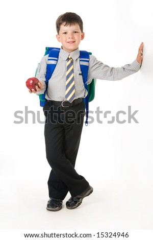 Portrait of diligent boy with apple and backpack standing in the studio - stock photo
