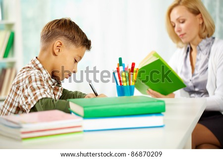 Portrait of diligent boy writing something with his tutor reading near by - stock photo