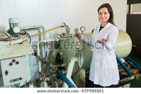Portrait of diligent female engineer near olive pressing engine inside factory