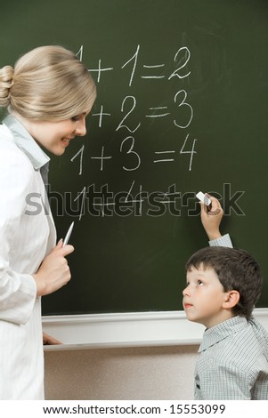 Portrait of diligent pupil looking at his teacher near blackboard while doing sums