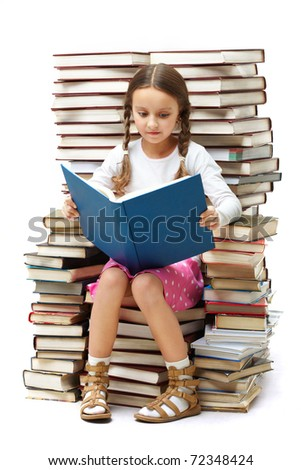 Portrait of diligent pupil sitting on pile of books and reading one of them - stock photo