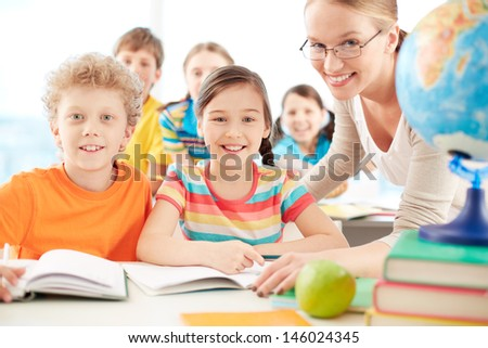 Portrait of diligent schoolkids and teacher looking at camera at lesson - stock photo