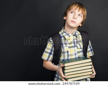 Portrait of diligent student in glasses with heap of books in hands - stock photo