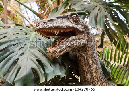 portrait of dinosaur figures in a wooded park - stock photo
