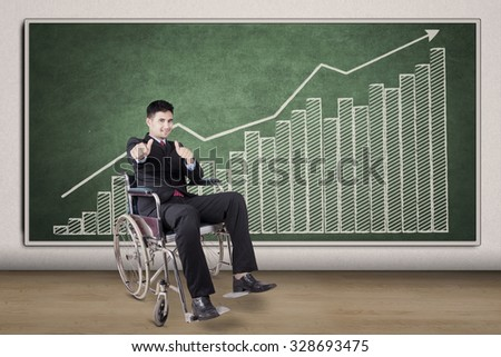 Portrait of disabled businessman showing hands gesture in front of financial chart - stock photo