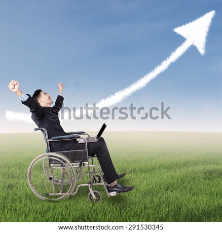 Portrait of disabled businessman sitting on wheelchair in nature with laptop and looks happy, celebrating his achievement under upward arrow - stock photo
