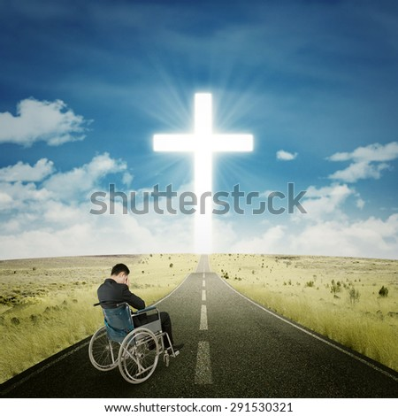 Portrait of disabled businessman sitting on wheelchair while praying on the road with a cross at the end of the road - stock photo