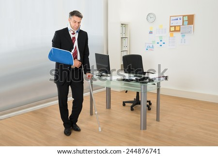 Portrait Of Disabled Businessman Standing With Crutches In Office - stock photo