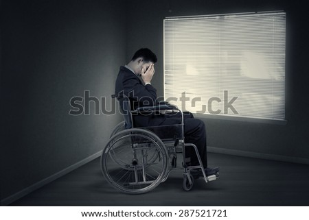 Portrait of disabled entrepreneur looks sad and sitting in wheelchair near the window - stock photo