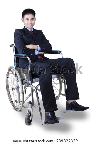 Portrait of disabled male entrepreneur wearing formal suit while sitting on wheelchair and looks confident - stock photo