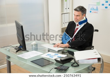 Portrait Of Disabled Mature Businessman On Wheelchair Using Computer At Office - stock photo