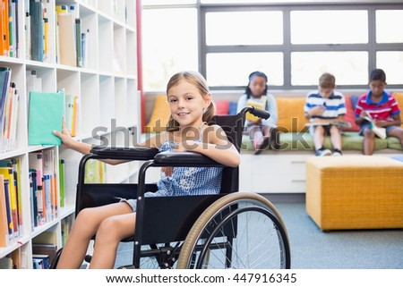 Portrait of disabled school girl selecting a book from bookshelf in library at school