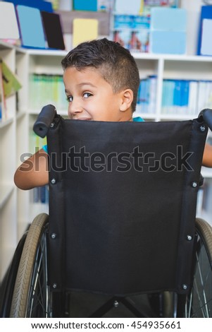 Portrait of disabled schoolboy in library at school - stock photo