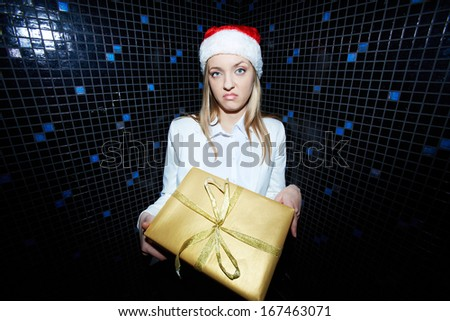 Portrait of displeased businesswoman in Santa cap holding Chistmas gift - stock photo