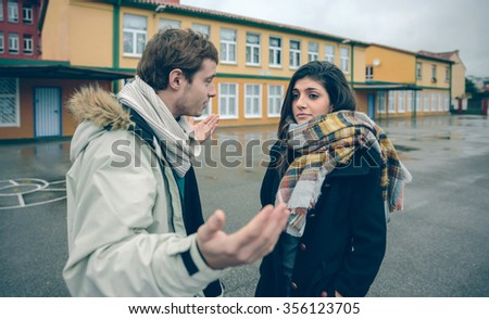 Portrait of dissapointed woman listening arguments of young man during a hard quarrel outdoors. Couple relationships and problems concept. - stock photo