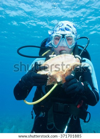 portrait of diver-girl with big seashell in a her hands