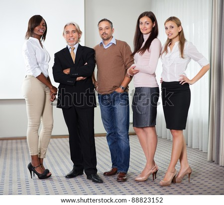 Portrait of diverse business group standing together in office