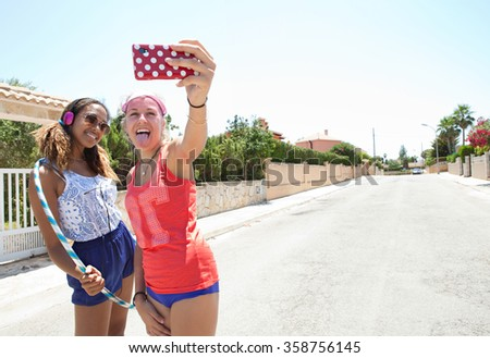 Portrait of diverse teenager friends posing together pulling faces taking a selfie in a suburban street wearing retro colorful clothes having fun, outdoors. Adolescents using smartphone technology. - stock photo