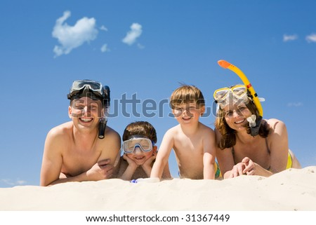 Portrait of diving family lying on sand against blue sky and smiling at camera