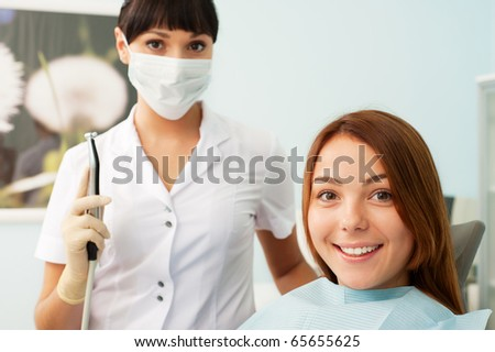 portrait of doctor and patient at dentist's office - stock photo