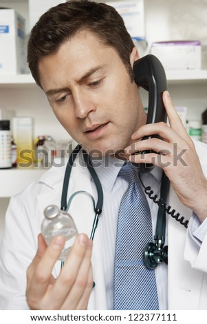 Portrait of doctor communicating on landline while looking at drug bottle - stock photo