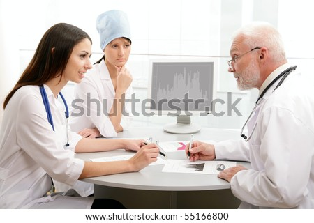 Portrait of doctor explaining computer work to coworkers - stock photo