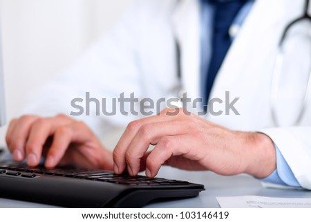Portrait of doctor hands on keyboard while using the computer at hospital workplace - stock photo
