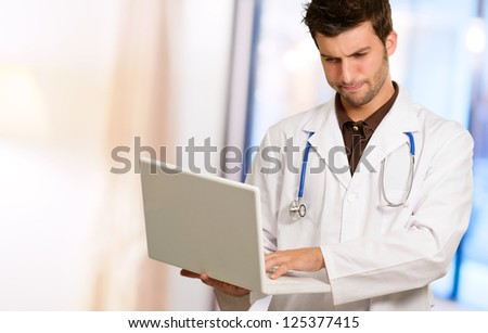 Portrait Of Doctor Holding Laptop, Indoors