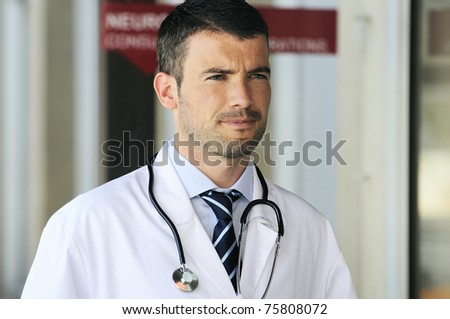 portrait of doctor in front an entrance of the hospital - stock photo