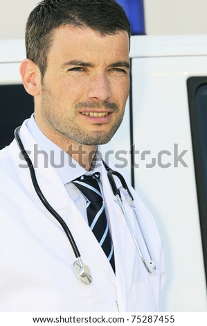 portrait of doctor in front of an ambulance - stock photo