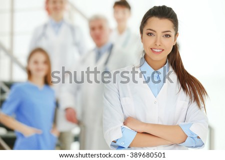 Portrait of doctor in front of colleagues indoors - stock photo