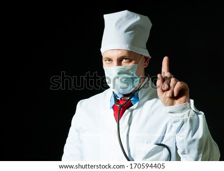 Portrait of doctor in surgical mask on black background