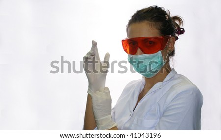 Portrait of doctor putting on her gloves before the operation (isolated on white) - stock photo