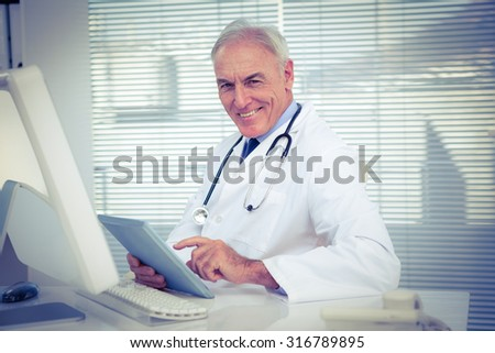 Portrait of doctor using digital tablet by computer at clinic - stock photo