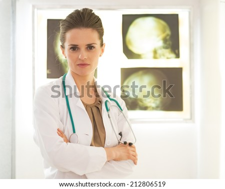 Portrait of doctor woman in front of lightbox - stock photo