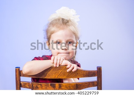 Portrait of dreaming little girl sitting on chair - stock photo