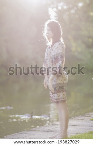 Portrait of Dreaming Romantic Girl Outdoors. Model With Long Stylish Hair Against Nature Background. Vertical Image