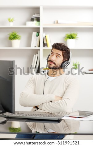 Portrait of dreamy creative man with headphone sitting at workplace. Young professional working at office while listening music online.