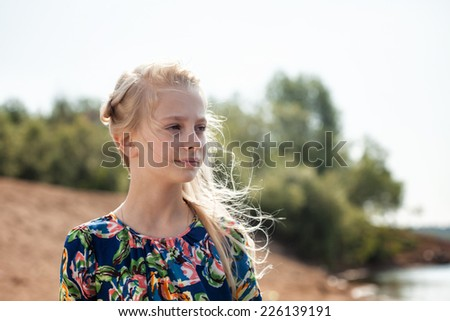 Portrait of dreamy girl with flying hair in wind - stock photo
