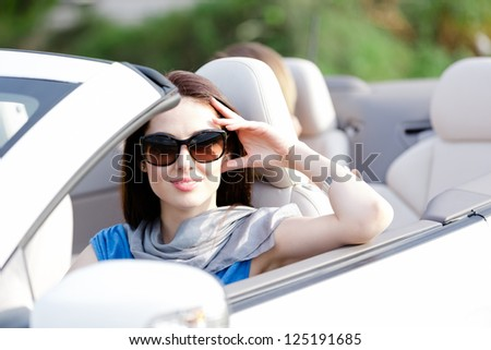 Portrait of dreamy woman wearing sunglasses in the cabriolet and propping her head - stock photo